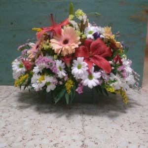 Centro de flores variadas realizado sobre caja de madera