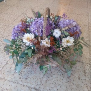 Cesta de mimbre adornado con flores de tela